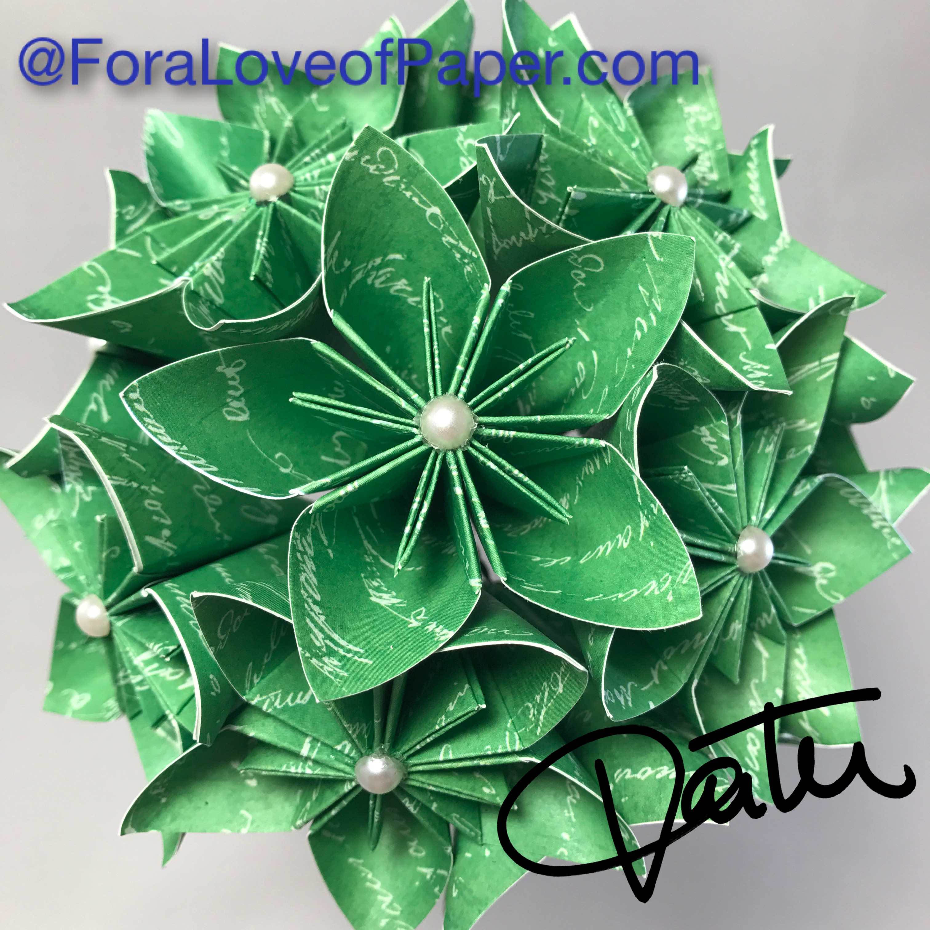 Paper flowers made from green paper with white script