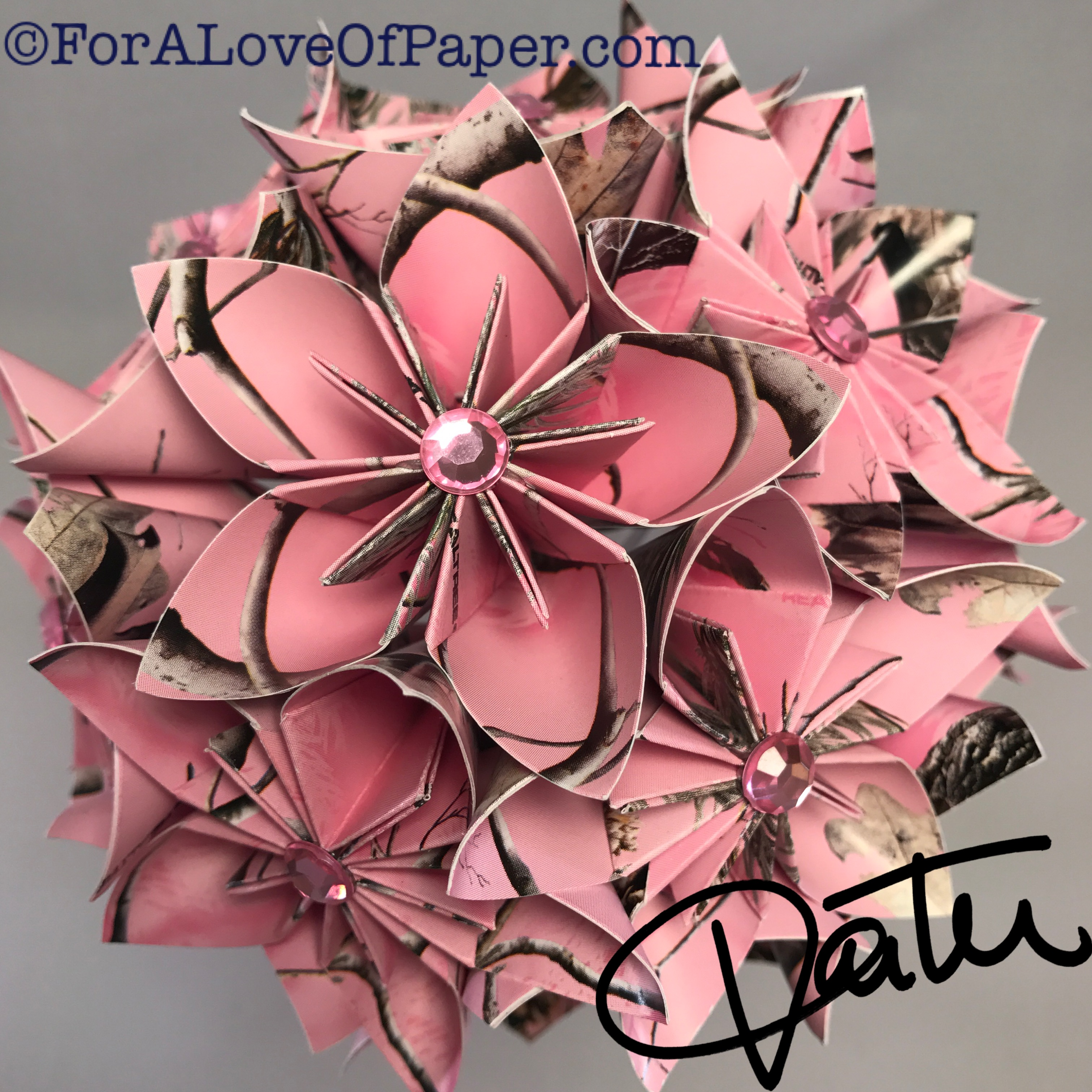 Paper flowers in pink camouflage themed scrapbook paper
